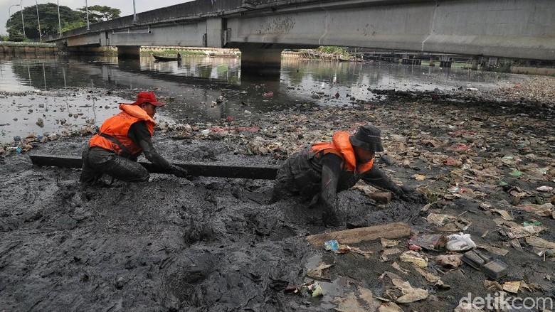 Aksi Petugas UPK Badan Air Mandi Lumpur Bersihkan Sampah