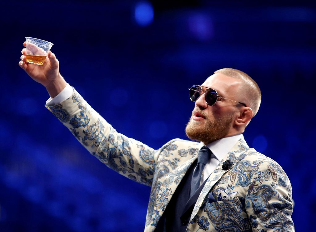 FILE PHOTO: UFC lightweight champion Conor McGregor of Ireland raises a cup of Irish whiskey during post-fight news conference at T-Mobile Arena in Las Vegas, Nevada, U.S. August 27, 2017. REUTERS/Steve Marcus/File Photo
