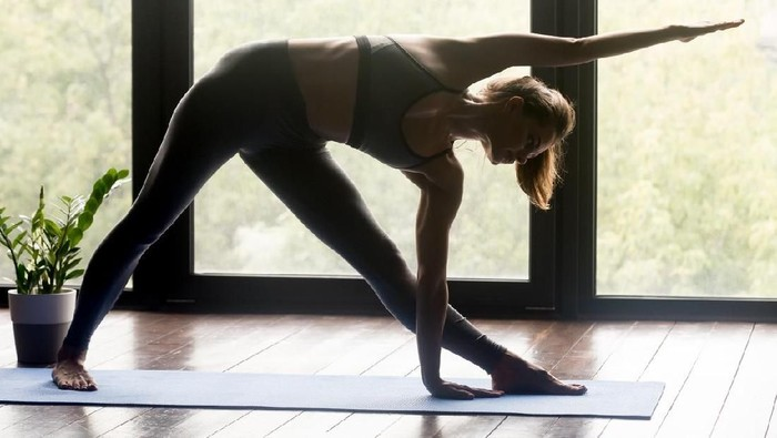 Young woman practicing yoga, doing head to knees, uttanasana exercise, Standing forward bend pose, working out, wearing sportswear, black pants and top, indoor full length, gray wall in yoga studio