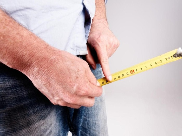 An unrecognizable mans hands hold a tape measure to the crotch of his jeans, checking size or growth with his forefinger.
