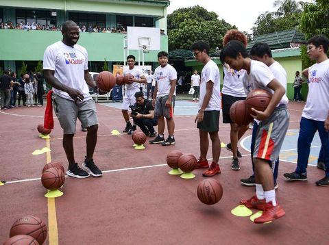 Mantan pebasket NBA Jason Richardson (kiri) memberikan pelatihan bola basket kepada siswa di SMA Negeri 82, Jakarta, Kamis (28/3/2019). Peraih dua gelar juara kontes slamdunk NBA itu memberikan pelatihan kepada siswa SMA Negeri 82 dalam rangka program Junior NBA. ANTARA FOTO/Hafidz Mubarak A/wsj.