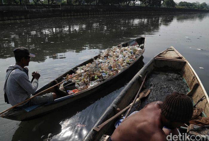 Sejumlah warga nampak sibuk mengumpulkan sampah menggunakan sampan di sekitara Kali Cagak, Kapuk Muara, Jakarta Utara, Kamis (28/3/2019).