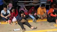 Sebagian penumpang menunggu kedatangan KRL dengan duduk lesehan di lantai peron Stasiun Tanah Abang.