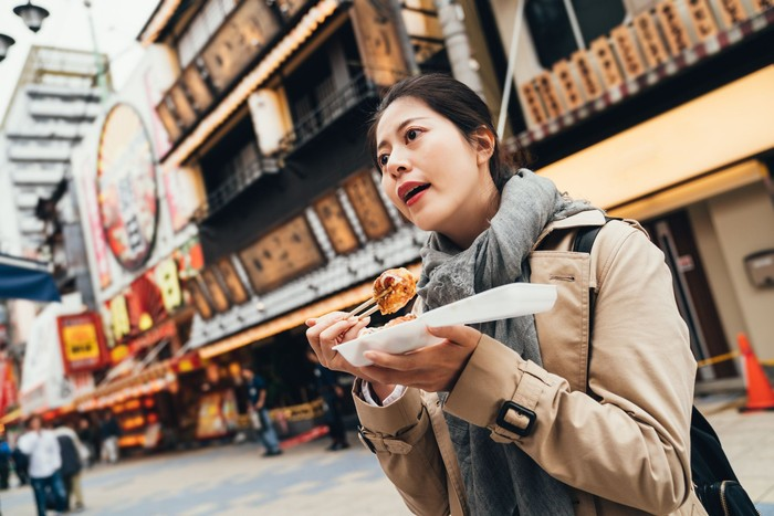 young asian woman holding box of japanese local street food looking around. lady traveler enjoy eating takoyaki on the road outdoor. delicious octopus balls in osaka japan.