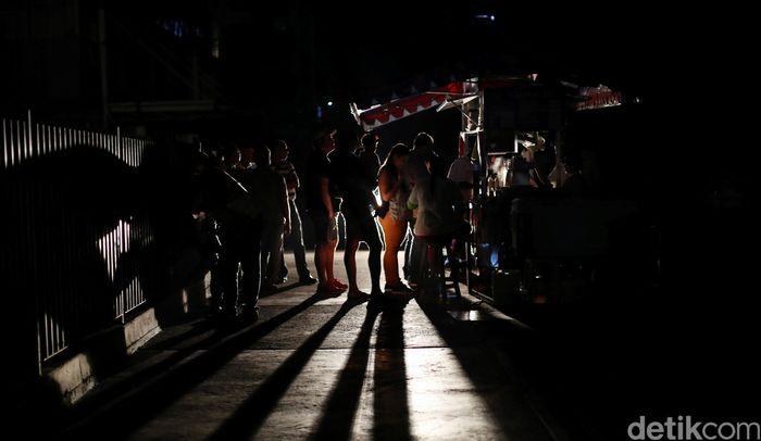 Penduduk setempat berkumpul di sebuah gerobak jajanan selama pemadaman listrik di Caracas, Venezuela.REUTERS/Ivan Alvarado