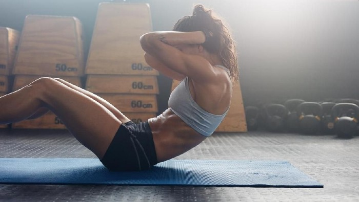 Sporty young female athlete on yoga mat doing sit up in gym. Fitness woman doing abs crunches.