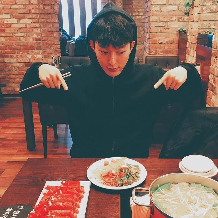 Jang Ki-yong terlihat sedang menikmati makanan Korea dengan mengenakan jaket hitam. Foto: Instagram@juanxkui