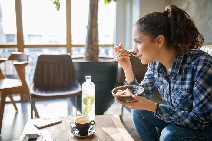 Woman eating cereals with yogurt for breakfast