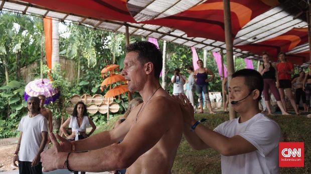 Instruktur yoga Ronan Tang saat membantu peserta mempraktikkan Qi Flow Yoga dalam gelaran Bali Spirit Festival 2019 di Ubud, Bali.