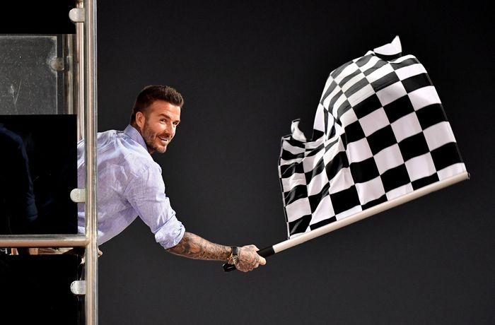 Bintang sepakbola Inggris David Beckham membuat penampilan tak terduga di ajang balapan F1 GP Bahrain pada Minggu (31/3/2019), ia menjadi pengibar bendera finis dalam acara tersebut. Andrej Isakovic/Pool via Reuters.