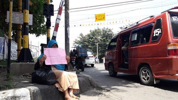 Sumiatu duduk di trotoar di dekat Stasiun Bekasi.