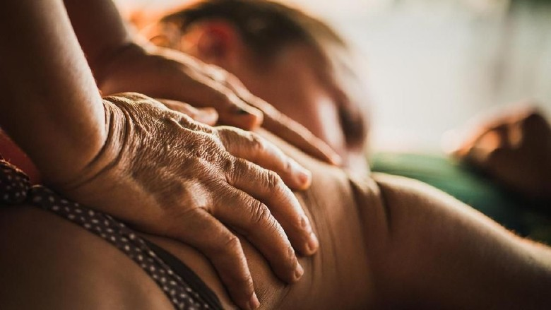 Unrecognizable massage therapist performing reflexology on her customer at beauty spa.