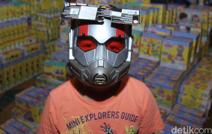 Seorang anak memakai topeng yang jadi buruannya.