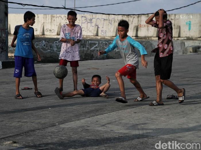Anak-anak di kawasan Muara Baru menjadikan jalan raya sebagai arena untuk bermain. Mereka bermain sepakbola hingga burung dara di jalan tersebut.
