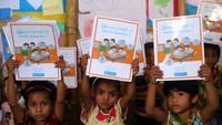 Anak-anak pengungsi Rohingya menunjukkan buku-buku mereka untuk belajar bahasa Burma di pengungsian Coxs Bazar, Bangladesh.