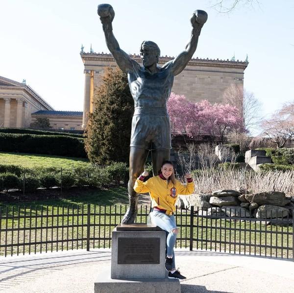 Sama seperti orang-orang pada umumnya, Michelle Waterson juga suka traveling keliling dunia. Ini saat dia berfoto di monumen Rocky Balboa, Philadelphia (Instagram/karatehottiemma)