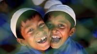 Dua orang anak nampak tersenyum ke arah kamera di sela-sela waktu belajar mereka.