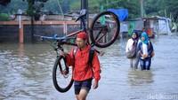 Sepeda pun harus dipanggul untuk melintasi jalan yang terendam banjir setinggi betis hingga lutut orang dewasa tersebut.