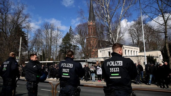 Policemen and mourners stand at the roadside, where a hearse transported the coffin of Thomas Haller, a leading figure in eastern Germanys far-right scene and fan of German fourth-tier football club Chemnitzer FC, to the cemetery in Chemnitz, eastern Germany, on March 18, 2019; in background can be seen the Michaeliskirche church. - A political storm was whipped up in Saxony state before a match on March 9, 2019 against Altglienicke when Chemnitz fans paid tribute before kick-off to Haller, who had for years provided security for the club and co-founded the HooNaRa (Hooligans-Nazis-Racists) group in the 1990s that was disbanded in 2007. (Photo by Ronny Hartmann / AFP)