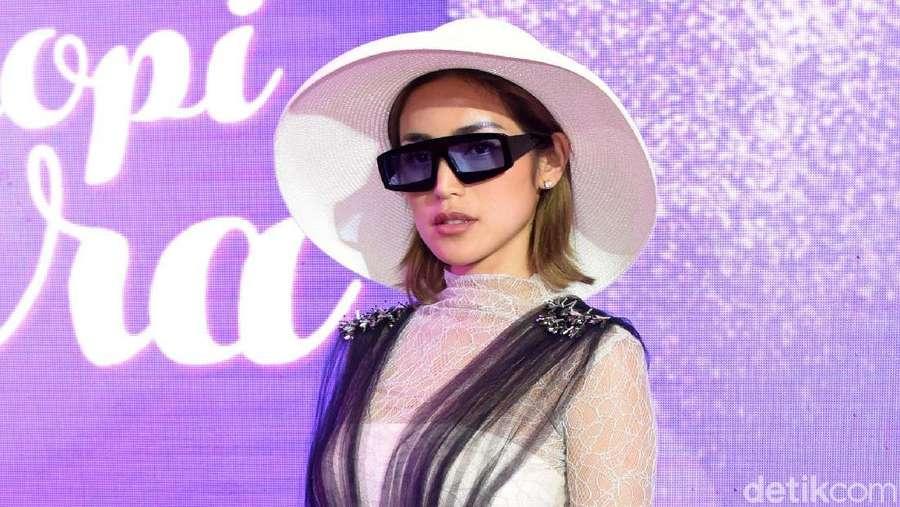 Gaya Jessica Iskandar dengan Topi Putih dan Kacamata Hitam