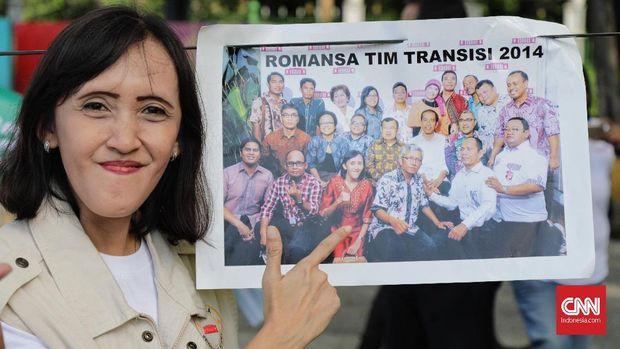 Seorang peserta aksi menunjukkan posisi dirinya dalam foto Tim Transisi.