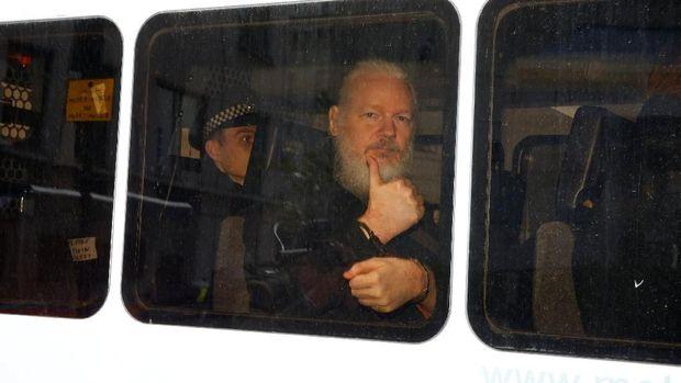 Assange mengacungkan jempol usai ditangkap di London
