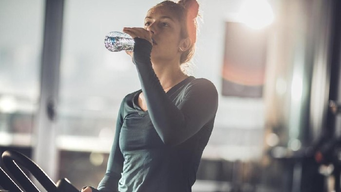 Tired female athlete drinking fresh water while resting from exercising class in a health club.