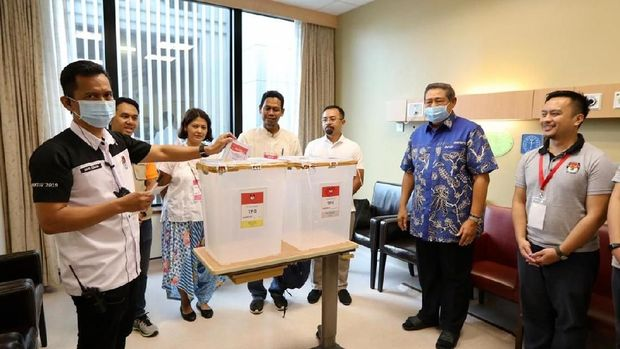 Petugas TPS PPLN Singapura memasukan surat suara yang dicoblos Ani di kotak suara.