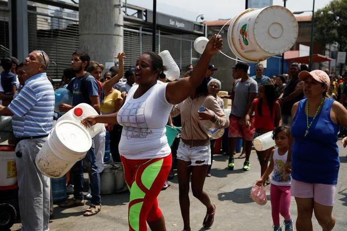 Orang-orang berteriak ketika mereka mengantri untuk mengambil air di sebuah jalan di Caracas.