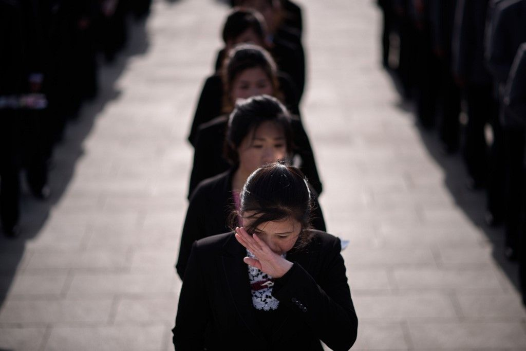 A woman talks on a mobile phone as Korean Peole's Army (KPA) soldiers arrive to pay their respects before the statues of late North Korean leaders Kim Il Sung and Kim Jong Il, as part of celebrations marking the anniversary of the birth of Kim Il Sung, known as the 'Day of the Sun', on Mansu hill in Pyongyang on April 15, 2019. (Photo by Ed JONES / AFP)