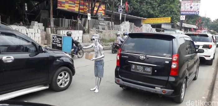 Dayat milih beraksi di tengah jalan antara baris kendaraan. Kinclong banget kan, kebayang nggak teriknya matahari waktu Dayat jadi manusia silver? (Foto: Rosmha/detikHealth)