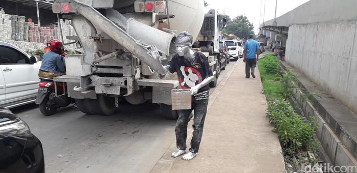 Ikhsan pasang gaya di pinggir jalan yang padat banget. Jadi manusia silver, Ikhsan kena semburan asap knalpot kendaraan bermotor tiap hari. (Foto: Rosmha/detikHealth)