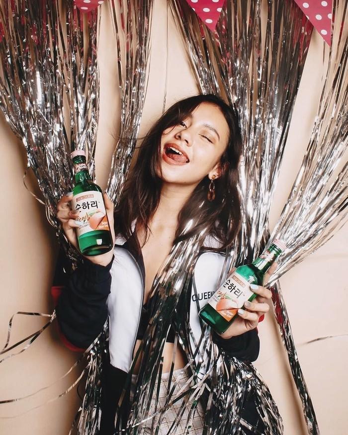 Aktris asal Bali ini memiliki paras yang cantik dan sering mengenakan pakaian seksi. Ia terlihat sedang memegang dua botol soju kesukaannya. Foto: Instagram@naomi.paulinda