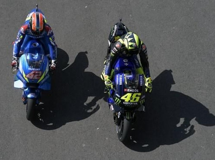 Italys biker Valentino Rossi (R) rides his Yamaha as Spains biker Alex Rins rides his Suzuki on pit lane during the MotoGP free practice of the Argentina Grand Prix at RioTermas de Rio Hondo circuit, in Santiago del Estero, Argentina on March 29, 2019. (Photo by JUAN MABROMATA / AFP)