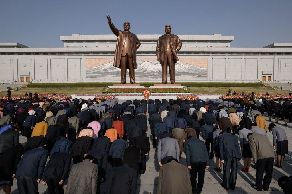 People bow as they pay their respects before the statues of late North Korean leaders Kim Il Sung and Kim Jong Il, as part of celebrations marking the anniversary of the birth of Kim Il Sung, known as the 'Day of the Sun', on Mansu hill in Pyongyang on April 15, 2019. (Photo by Ed JONES / AFP)