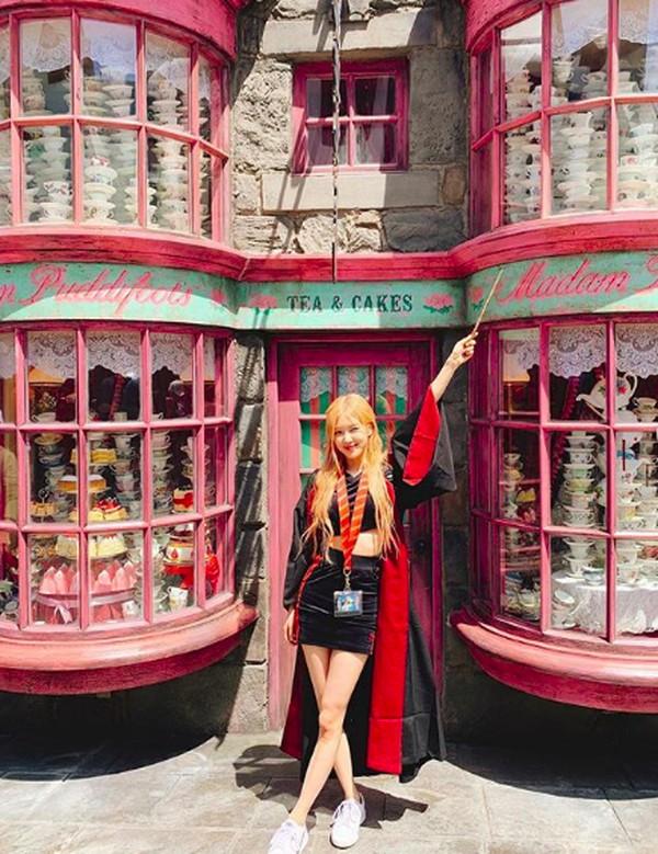 Adapun foto lain yang dibagikan Rose di Instagramnya, dia memegang minuman dan berfoto dengan latar kastil Harry Potter. (roses_are_rosie/Instagram)