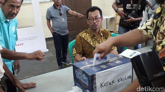 I Wayan Suardana melakukan pendampingan pada ODGJ saat Pemilu pada Rabu (17/4/2019). (Foto: Rosmha/detikHealth)