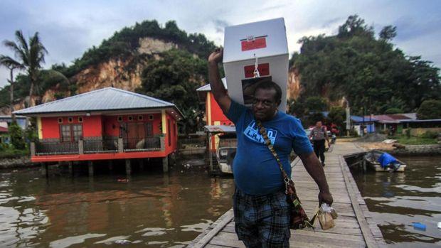 Petugas membawa kotak suara ketika melakukan pendistribusian logistik Pemilu 2019 di Kampung Kayu Pulo, Jayapura, Papua, Selasa (16/4).