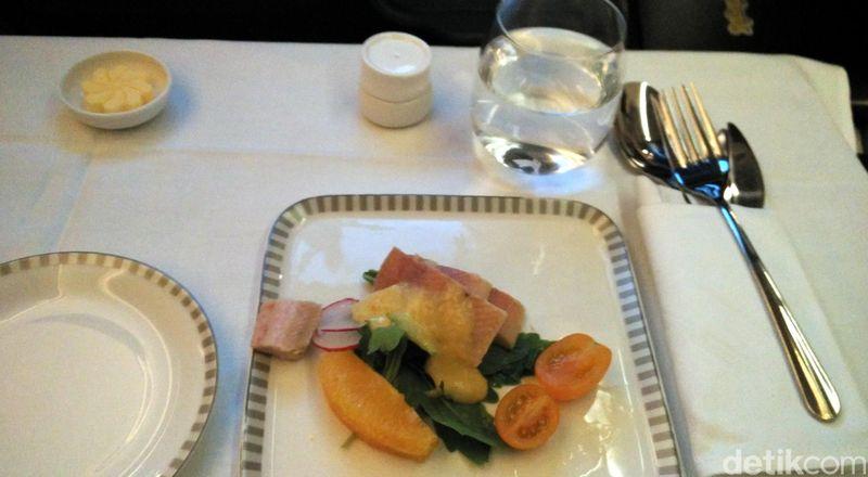 Di kelas bisnis, dihidangkan 3 set menu dinner. Dimulai dengan salad salmon seperti ini. (Wahyu Setyo/detikcom)