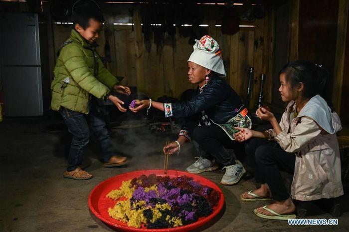 Seorang warga desa tengah memberikan beras berwarna kepada anak-anak di Desa Banjiang. Foto: Dok. Xinhuanet