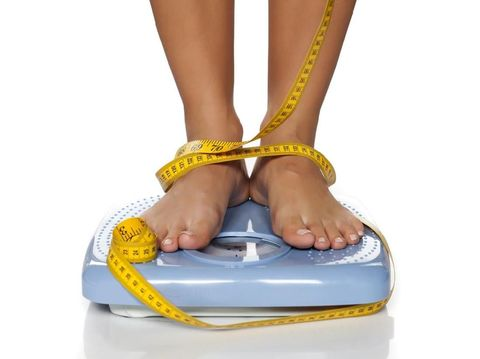woman's feet on a domestic weight scale and measuring tape around them