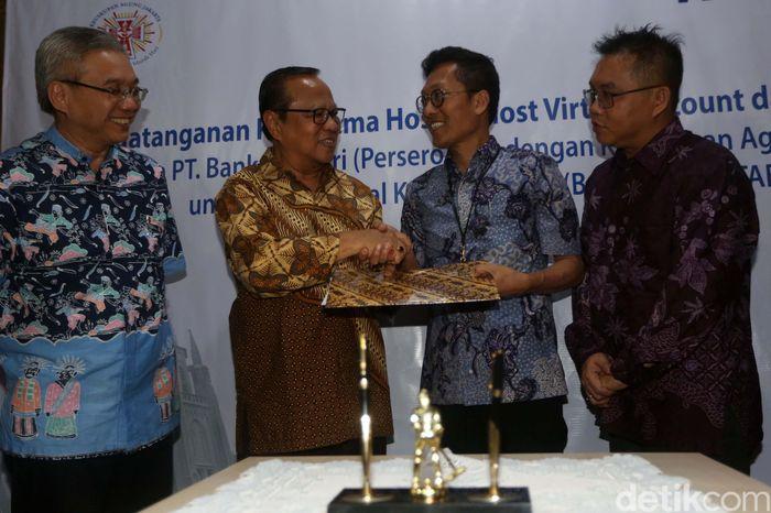 Direktur Teknologi Informasi & Operasi Bank Mandiri Rico Usthavia Frans (tengah) berbincang dengan Uskup Agung Jakarta Mgr. Dr. Ignatius Suharyo Hardjoatmodjo (kedua kiri) usai melakukan penandatanganan perjanjian kerjasama di Jakarta, Senin (22/4/2019).