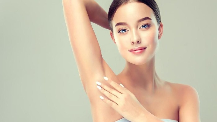 Gorgeous, young, blue-eyed woman  is touching the clean, soft skin of own armpit. Pure womans beauty. Facial and skin treatment, cosmetology, beauty technologies and armpit epilation.