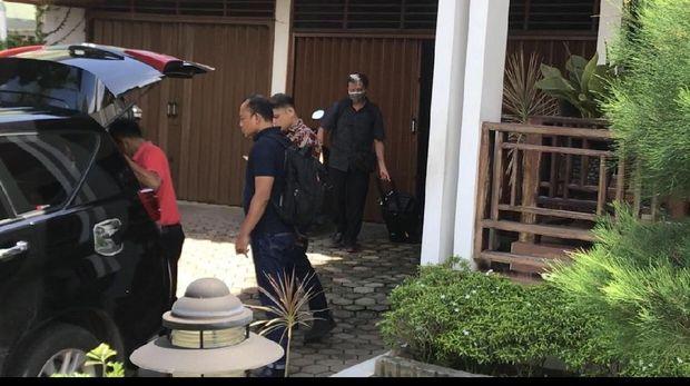 Seorang petugas membawa keluar koper berwarna hitam dari dalam rumah Muzni.