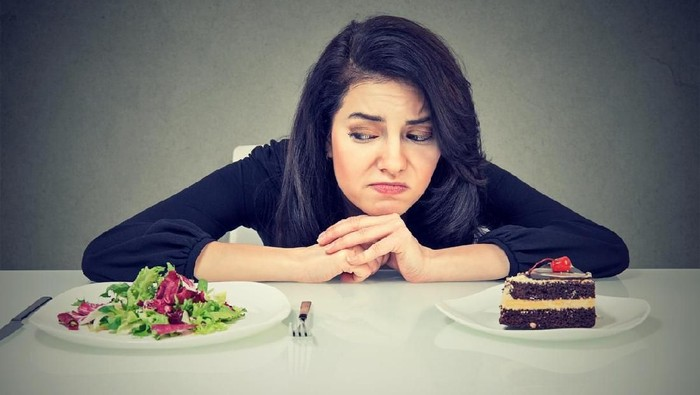 Beautiful brunette sitting at desk and suffering from choice between healthy salad and sweet dessert