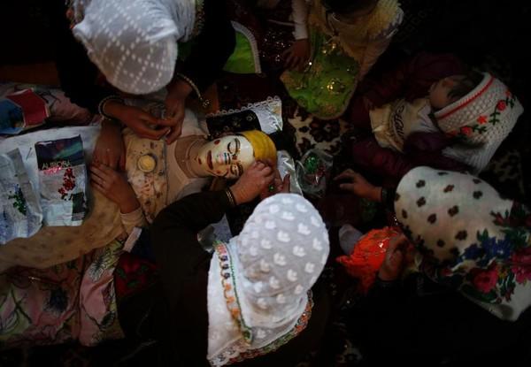 Mempelai wanita harus berbaring terlebih dahulu. Kemdian perias akan mulai mengecat wajah calon pengantin dengan warna putih. (REUTERS/Stoyan Nenov)