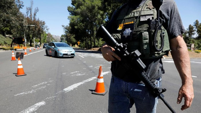A San Diego County Sheriff's Deputy secures the scene of a shooting incident at the Congregation Chabad synagogue in Poway, north of San Diego, California, U.S. April 27, 2019.  REUTERS/John Gastaldo