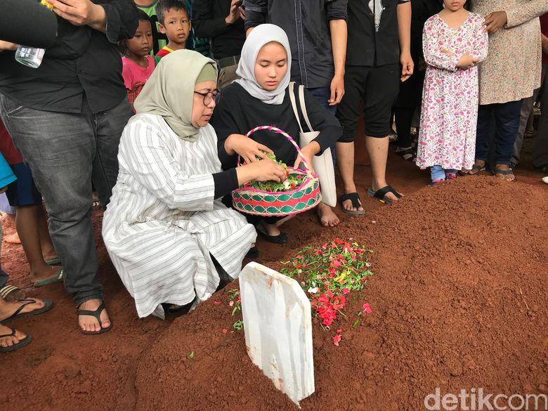 Sang istri dan putri almarhum tampak menaburkan bunga di pusara pesinetron tersebut.