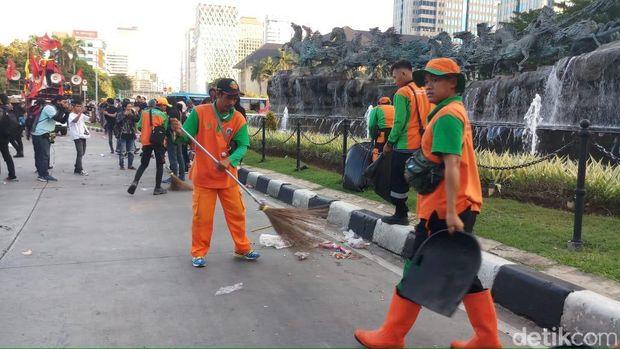 Pasukan oranye bersih-bersih usai Hari Buruh di Patung Kuda