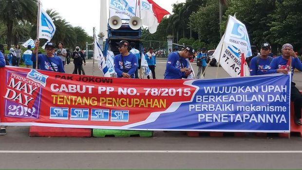 Massa buruh juga membentangkan spanduk bertuliskan 'cabut PP No 78/2015'.